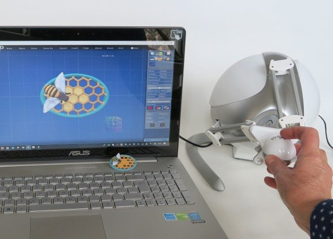 Anarkik3DDesign for PC and MAC: virtual 3D touch 3D modelling package: laptop with digital design of a 'bee' pin, Falcon haptic device and 3D printed 'bee' pin.